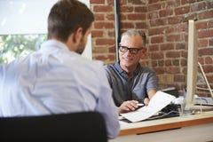 Affärsman Interviewing Male Job Applicant In Office Arkivbilder