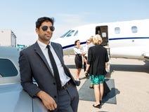 Affärsman Leaning On Car på flygplatsterminalen royaltyfri bild