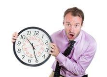 Affärsman ledare, ledare som rymmer en klocka, mycket beslutsamt som pressas av brist av tid som kör ut ur tid, sent för mötet Arkivfoton