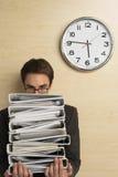 Affärsman Looking At Clock på träväggen fotografering för bildbyråer