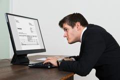 Affärsman Looking At Invoice på datoren Royaltyfri Fotografi