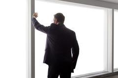 Affärsman Looking Out ett stort fönster Arkivbild