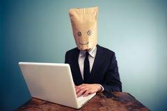 Affärsman med över huvudet arbete för påse på datoren Royaltyfri Bild
