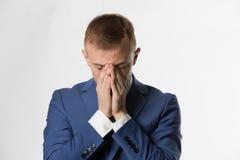 Affärsman med att rymma hans huvud i händer i skam arkivfoton