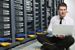 Affärsman med bärbar dator i lokal för nätverksserver Arkivbild