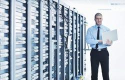 Affärsman med bärbar dator i lokal för nätverksserver Royaltyfri Foto