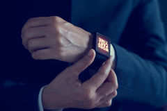 Affärsman med deltids- ord för arbete på smartwatchskärmen Arkivfoton