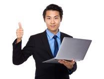 Affärsman med den bärbar datordatoren och tummen upp Arkivbilder