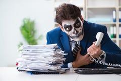 Affärsman med den läskiga framsidamaskeringen som i regeringsställning arbetar Royaltyfri Bild