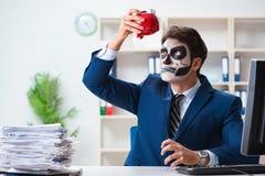 Affärsman med den läskiga framsidamaskeringen som i regeringsställning arbetar Arkivfoton