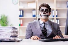Affärsman med den läskiga framsidamaskeringen som i regeringsställning arbetar Arkivfoto