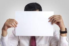 Affärsman med den tomma pappers- maskeringen som täcker hans framsida arkivfoton