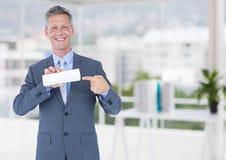 Affärsman med det lilla tomma kortet i oskarpt kontor Royaltyfri Fotografi