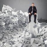 Affärsman med det pappers- arket någonstans Begravt av byråkratibegrepp arkivbilder