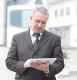 Affärsman med digitalt minnestavlaanseende nära kontorsbyggnad arkivfoton