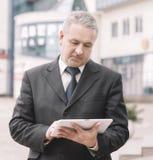 Affärsman med digitalt minnestavlaanseende nära kontorsbyggnad arkivfoto
