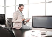 Affärsman med digitalt minnestavlasammanträde på kontorsskrivbordet royaltyfria bilder