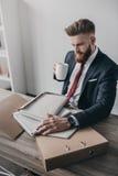 Affärsman med dokument och mappar som dricker kaffe och i regeringsställning sitter på tabellen Royaltyfri Foto