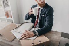 Affärsman med dokument och mappar som dricker kaffe och i regeringsställning sitter på tabellen Fotografering för Bildbyråer