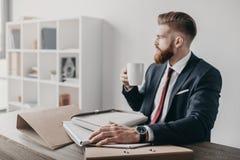 Affärsman med dokument och mappar som dricker kaffe och i regeringsställning sitter på tabellen Arkivbilder