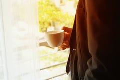 Affärsman med dräktställningen och den hållande kaffekoppen royaltyfri foto