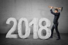 Affärsman med en hammare som bryter en sten '2018 'tecken på grå bakgrund royaltyfria foton