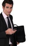 Affärsman med en mobiltelefon Fotografering för Bildbyråer
