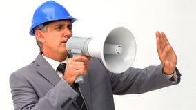 Affärsman med en säkerhetshjälm och en megafon stock video