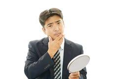 Affärsman med en spegel Royaltyfri Foto