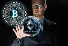 Affärsman med ethereum- och bitcoinhologram Arkivbilder