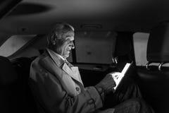 Affärsman med ett digitalt minnestavlasammanträde i baksätet av en bil Arkivfoton