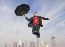 Affärsman med ett paraply i Midair royaltyfri bild