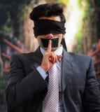 Affärsman med ett svart band i hans mun som gör ett tystnadtecken med ett finger in från av hans mun, i ett suddigt Arkivbilder