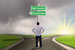 Affärsman med ett tecken av rätten vs fel beslut arkivbilder