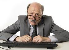 Affärsman med flinten på hans funktionsdugliga stressat för 60-tal och frustrerat på skrivbordet för bärbar dator för kontorsdato royaltyfri foto