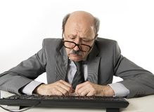 Affärsman med flinten på hans funktionsdugliga stressat för 60-tal och frustrerat på skrivbordet för bärbar dator för kontorsdato royaltyfri fotografi