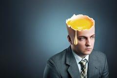 Affärsman med gul äggistead av huvudet fotografering för bildbyråer