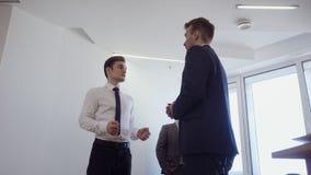 Affärsman med hans kollegaställningar i regeringsställning och att diskutera arbete stock video