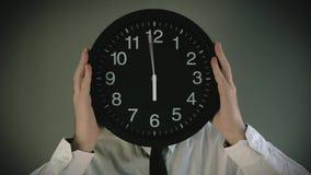 Affärsman med klockan som är främst av hans huvud lager videofilmer