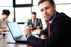 Affärsman med kollegor i bakgrund arkivbild