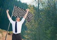 affärsman med kontrollörflaggan i berget royaltyfria bilder