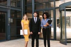 Affärsman med kvinnliga kollegor i företags kontorsbyggnad royaltyfri bild