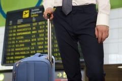 Affärsman med lopppåsen över flygplatsbakgrund royaltyfri bild