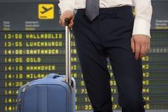 Affärsman med lopppåsen över flygplatsbakgrund royaltyfria bilder