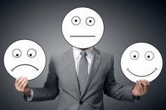 Affärsman med maskeringen av olika sinnesrörelser Affärsmaninnehavleende och ledsen maskering Begreppsmässig bild av en man som ä arkivbilder