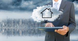 Affärsman med minnestavlan och molnet med huset mot oskarp horisont arkivbild