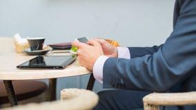Affärsman med minnestavlan och smartphonen under frukosten. Arkivfoto