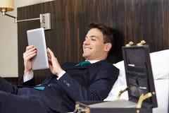 Affärsman med minnestavlaPC i hotellrum fotografering för bildbyråer