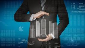 Affärsman med modellen 3d av staden och grafer Arkivbild