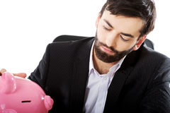 Affärsman med piggybank vid ett skrivbord Royaltyfri Fotografi
